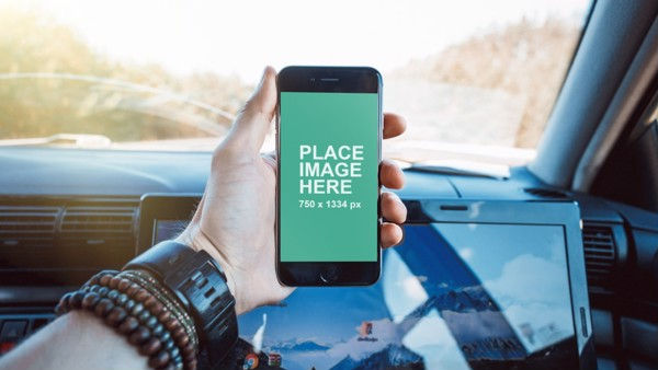 Man holding iPhone in car