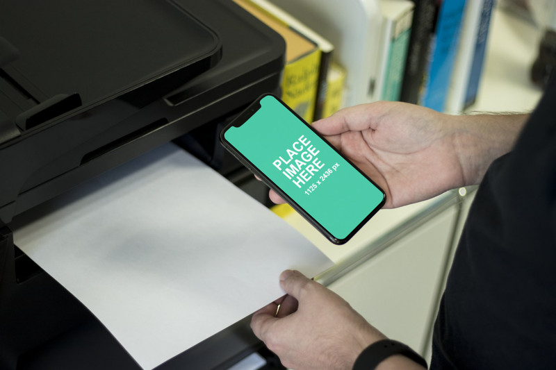 Man holding iPhone X at printer