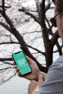 Man holding iPhone X in forest