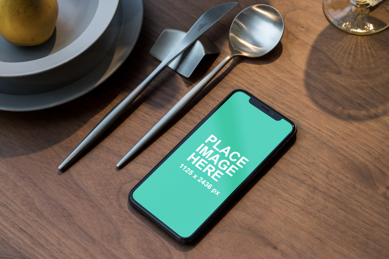 iPhone X with spoon and knife