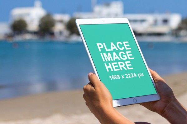 Woman using iPad on beach