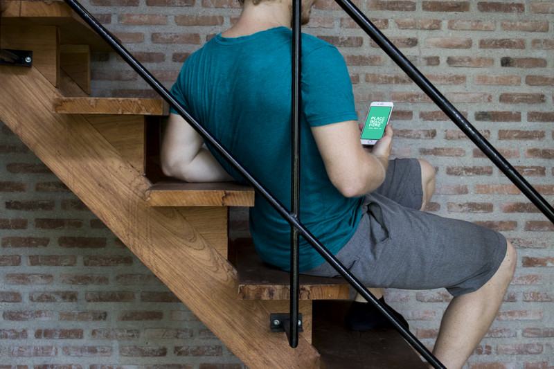 Man looking at iPhone on stairs