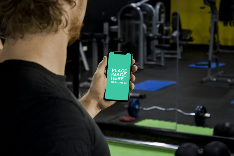 Man holding iPhone X in gym