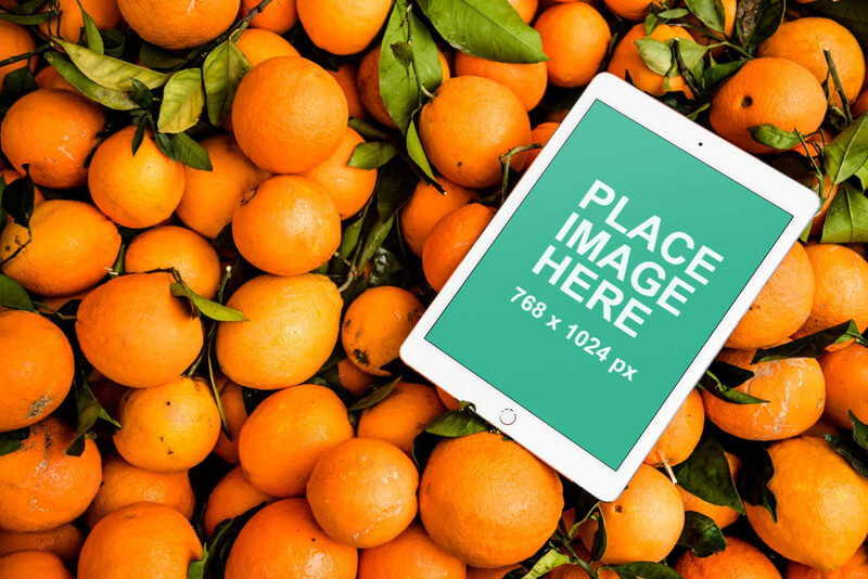 iPad on bed of oranges