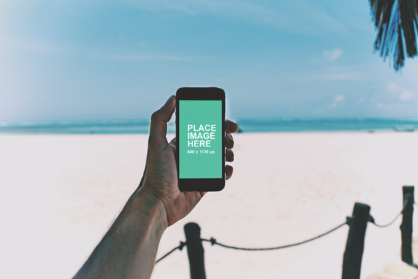 Man holding iPhone at beach
