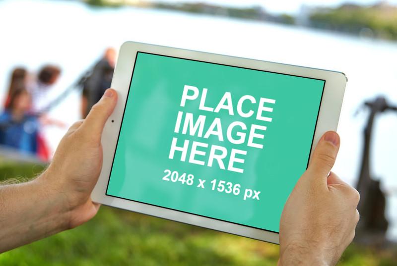 Man holding white iPad air in a park