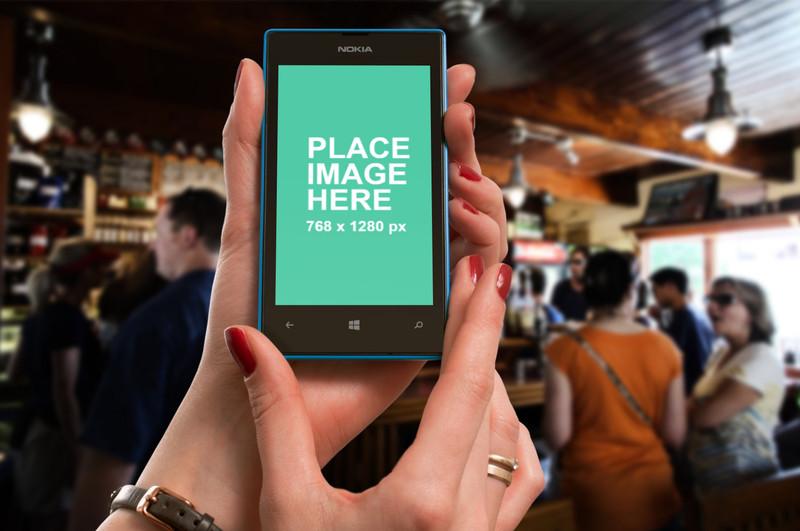 Woman holding Nokia Lumia at bar