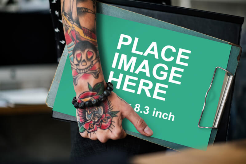 Tattooed woman holding A4 paper