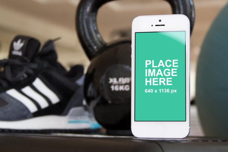 White iPhone 5 on gym floor