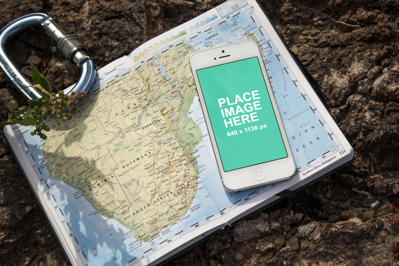 White iPhone 5 outside on world map