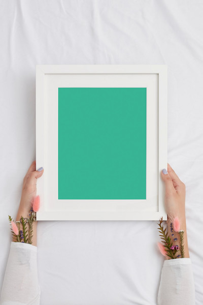Woman holding white frame