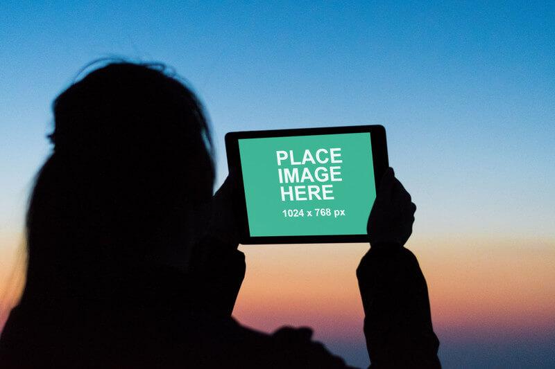 Woman using iPad at dusk